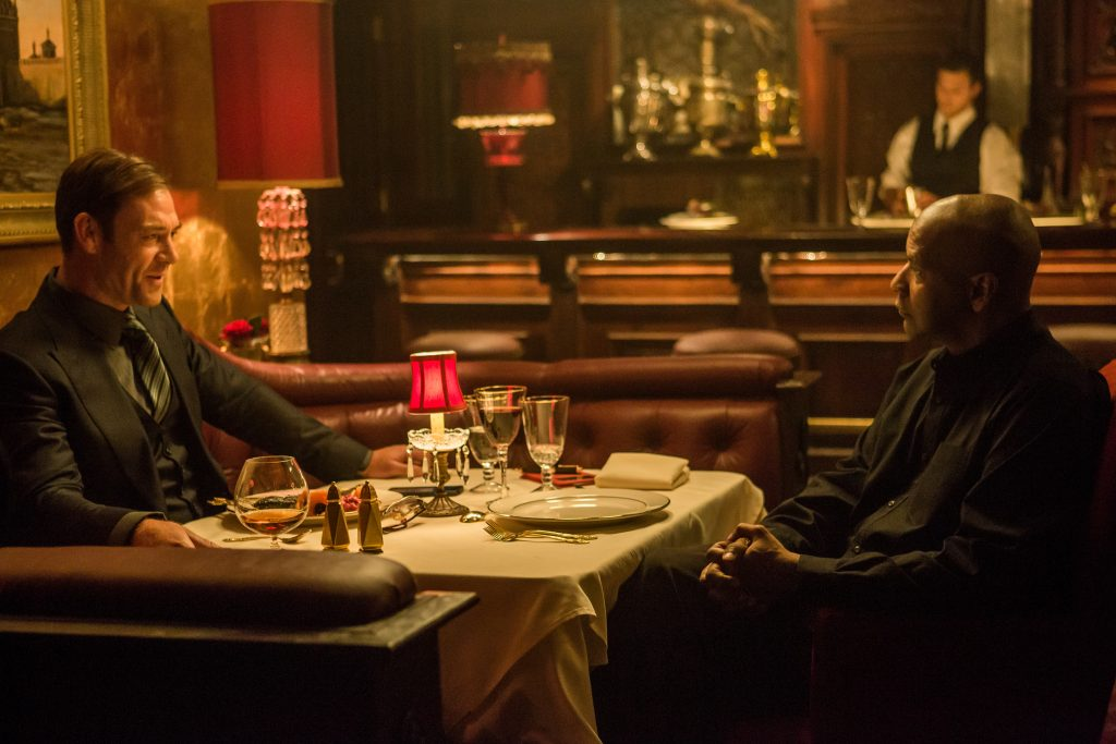 Marton Csokas and Denzel Washington sit at a table in a dimly lit restaurant