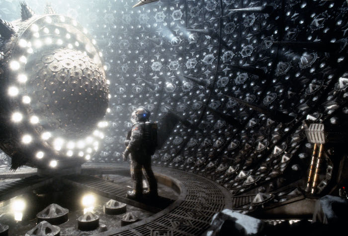 An astronaut stands in front of an ominous sphere in Event Horizon