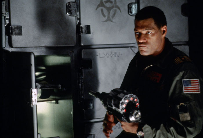 Laurence Fishburne, in a jumpsuit with an American flag, retrieves an item from a locker in Event Horizon