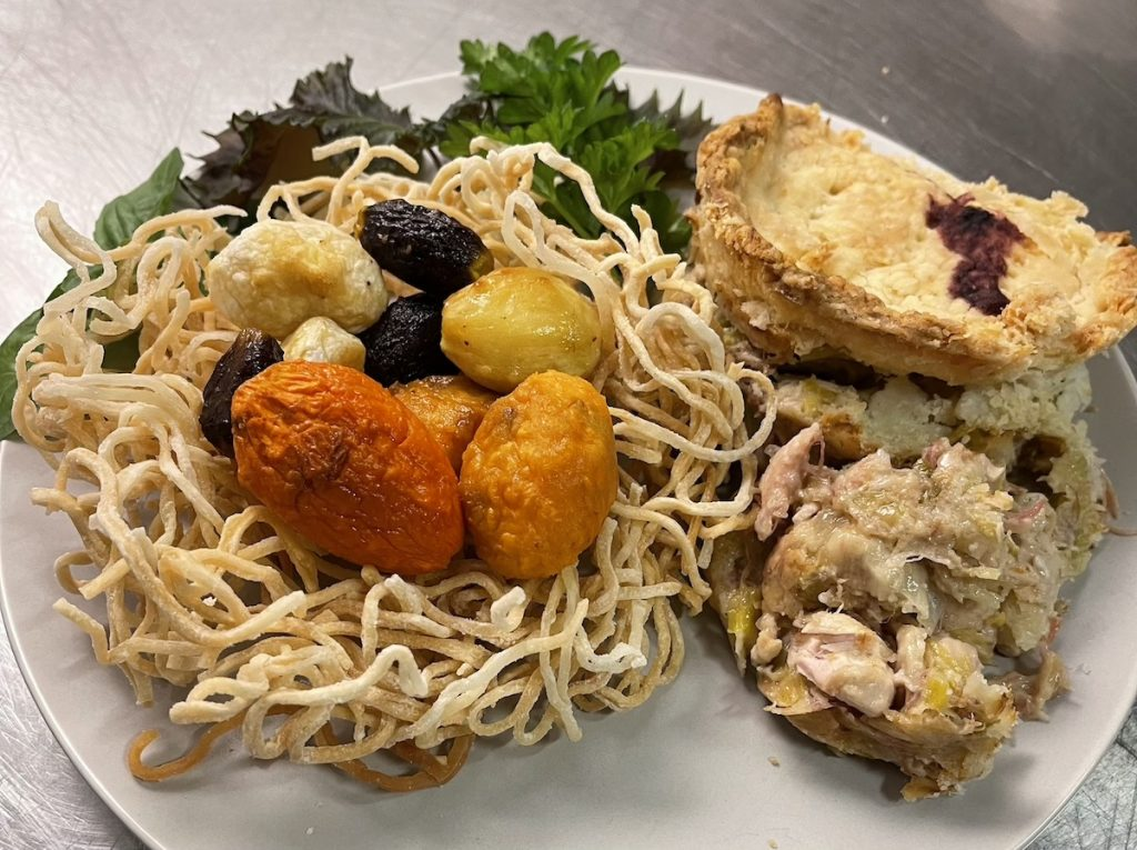 A plate with a serving of pot pie next to a roasted root vegetables carved into eggs served in a nest of fried noodles
