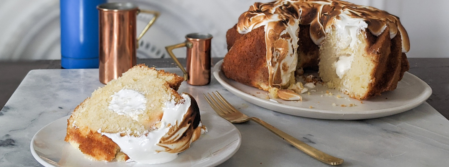 A slice of cake resembling a large Twinkie with a toasted marshmallow top