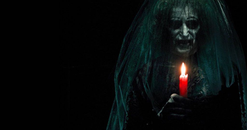 A hideous witch wearing a veil holds a lit candle in Insidious