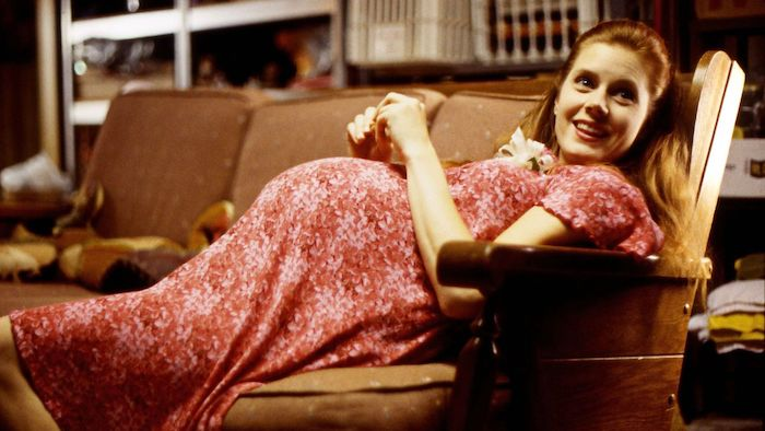 Amy Adams, pregnant, reclines on a sofa in Junebug
