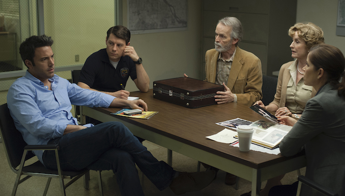 DF-11318_11319_COMP_R -- Nick (Ben Affleck, left) is questioned about the disappearance of his wife, Amy, by Detectives Boney (Kim Dickens, far right) and Gilpin (Patrick Fugit, in dark shirt), as Nick's in-laws Marybeth and Rand Elliott (Lisa Barnes, David Clennon) look on.