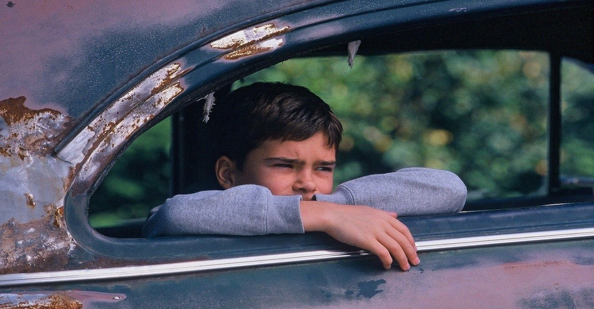 A child sits in the back seat of a rusted car, looking out the window