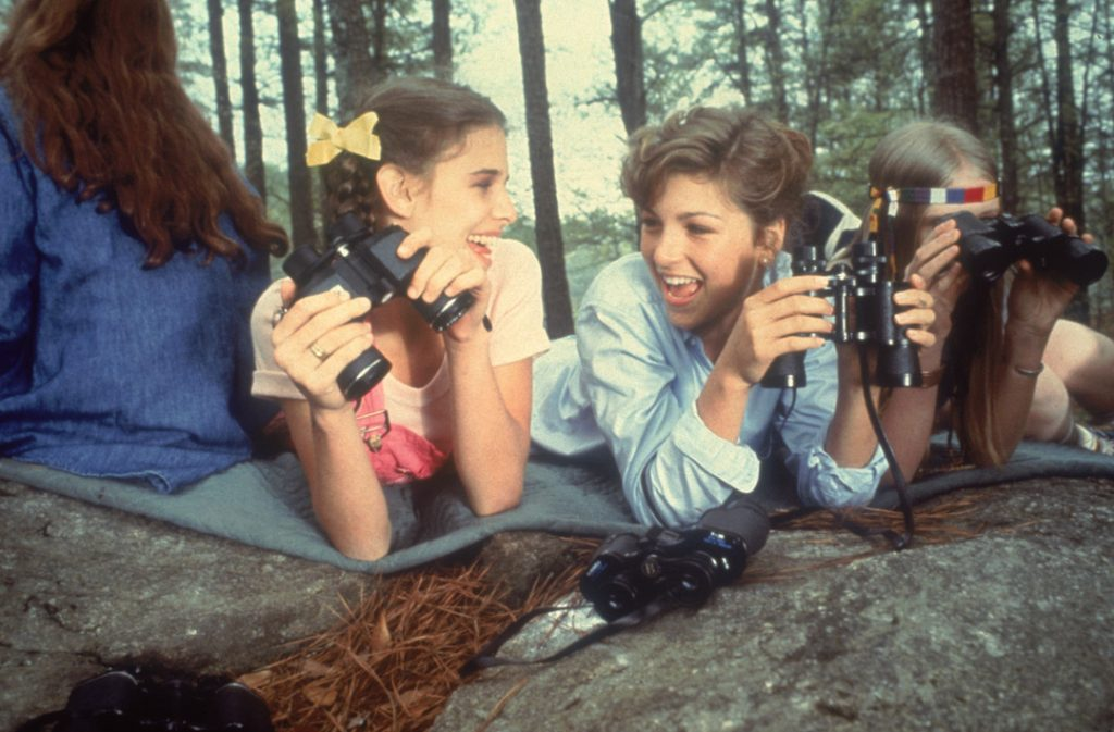 Female campers smile and laugh as they spy on other girls in Little Darlings