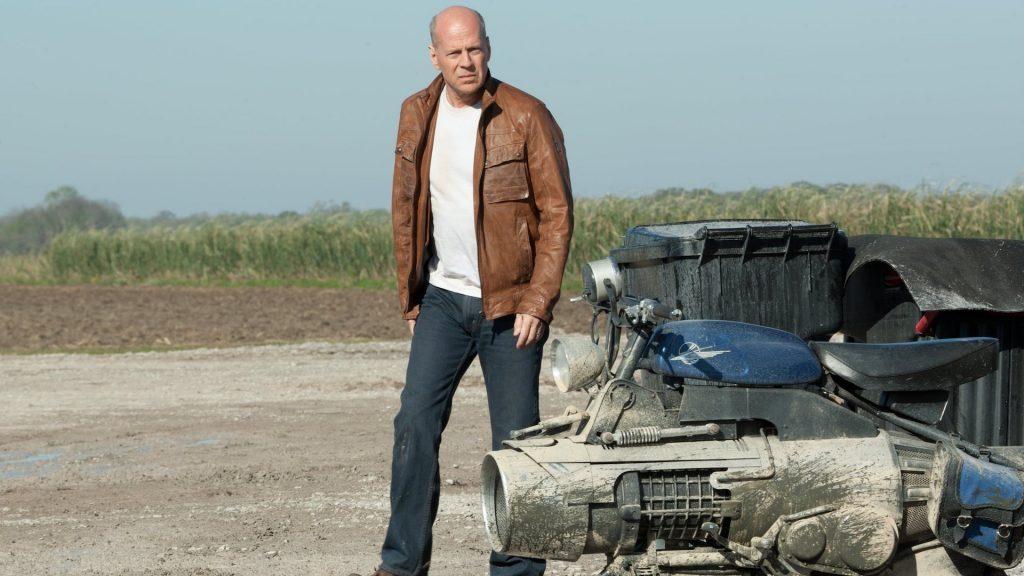 Bruce Willis walks toward a futuristic motorcycle in Looper