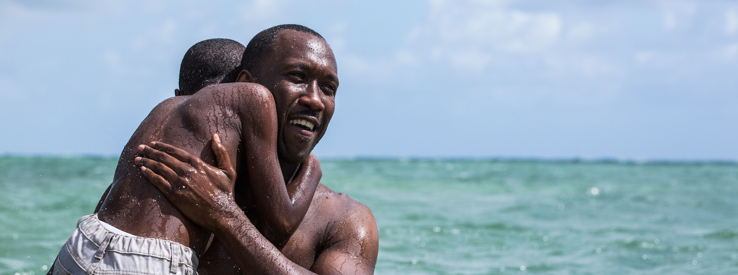 An image of Mahershala Ali carrying a boy through water in the film Moonlight