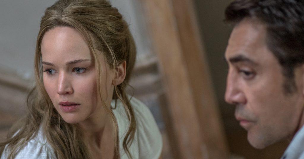 Jennifer Lawrence, looking startled, sits facing Javier Bardem