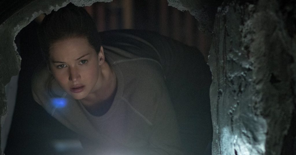 Jennifer Lawrence peers into a darkened hole in a wall