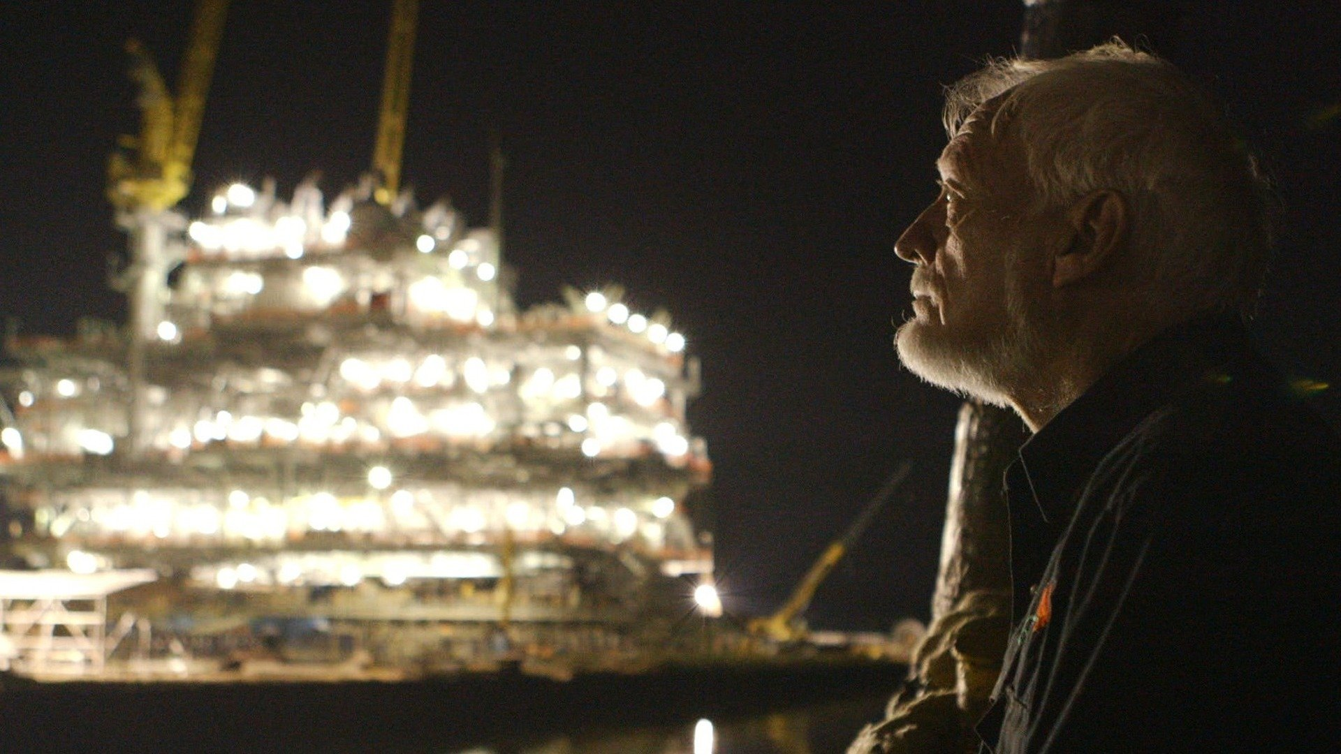 A night a man stands in silhouette in front of the blazing lights of an oil rig
