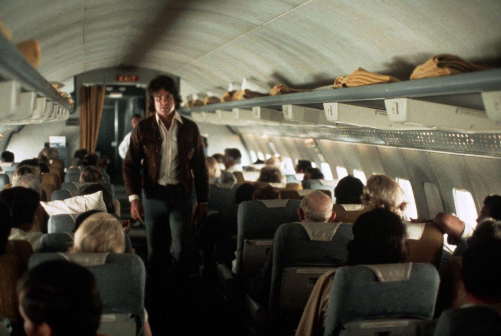 warren beatty walks back through the aisle on an airplane