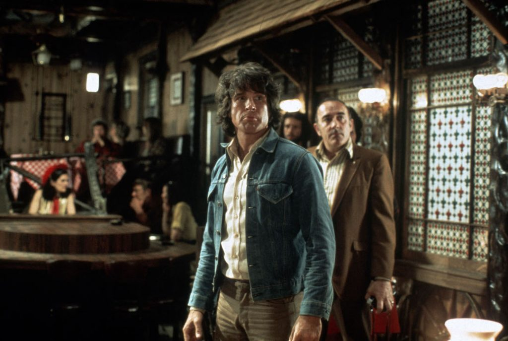 Warren Beatty stands in a wood-panelled restaurant in The Parallax View