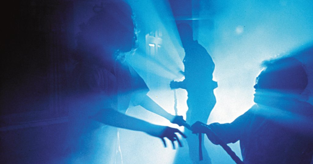 Silhouettes of ghostly figures in a misty scene in Poltergeist