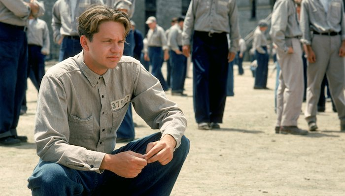 Andy (Tim Robbins)squats in the prison yard in The Shawshank Redemption