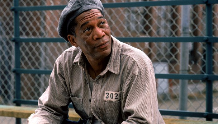 Ellis (Morgan Freeman)sits on bleachers in the prison yard in The Shawshank Redemption