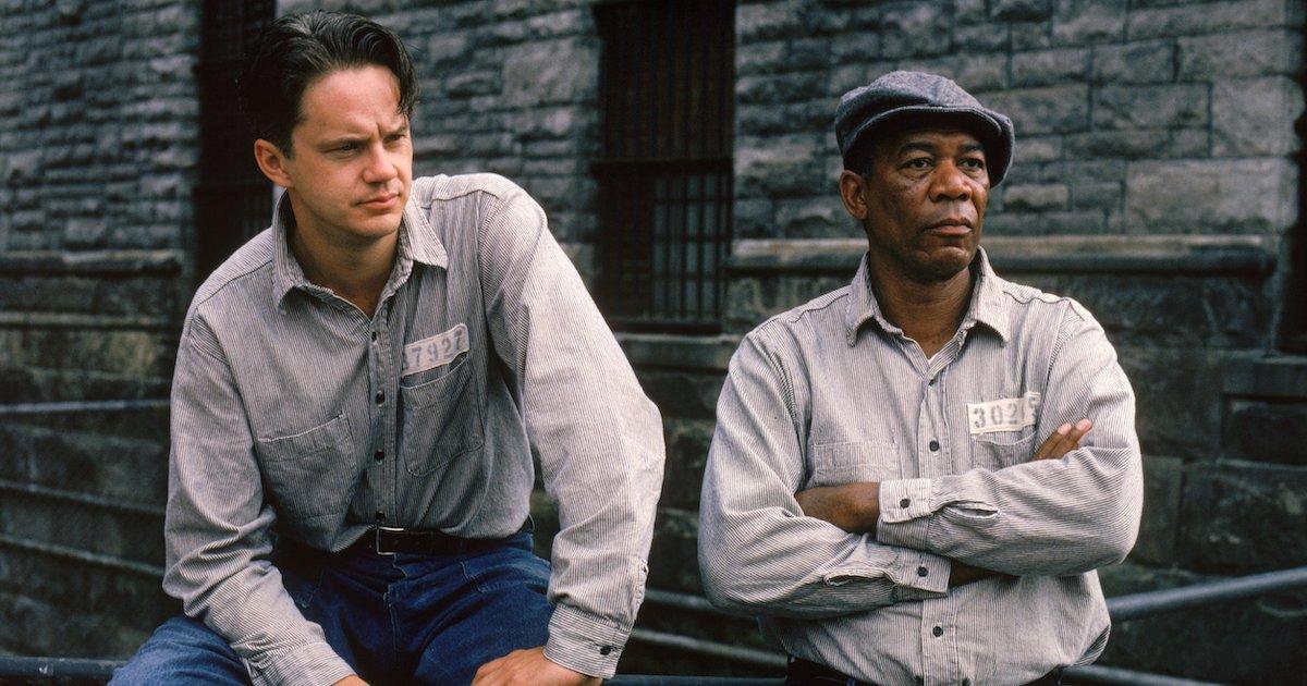 Andy (Tim Robbins) and Ellis (Morgan Freeman) lean against a railing in the prison yard in The Shawshank Redemption