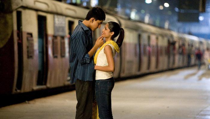 Dev Patel and Freida Pinto embrace on a train platform in Slumdog Millionaire