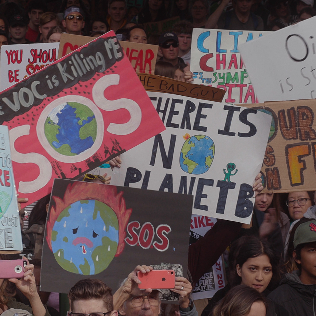 Young people hold signs at a climate change protest