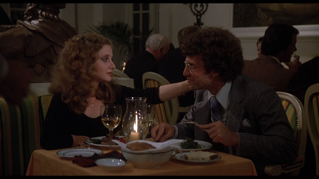 An adult Carol Kane has dinner in a restaurant with her husband