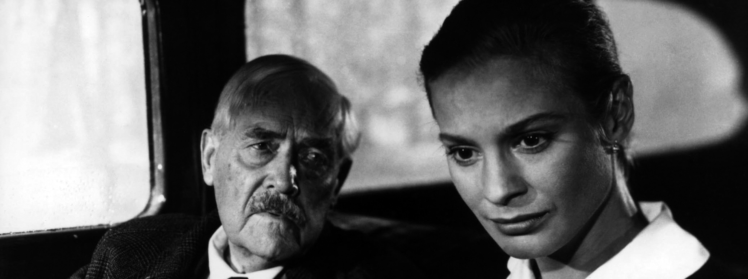 Victor Sjöström as Doctor Isak Borg looks at Ingrid Thulin as his daughter in the back of a car in Wild Strawberries
